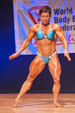 Female bodybuilder flexes her muscles to show her physique Royalty Free Stock Photo