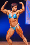 Female bodybuilder flexes her muscles to show her physique Royalty Free Stock Image