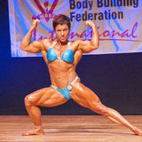 Female bodybuilder flexes her muscles to show her physique Stock Photos