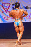 Female bodybuilder flexes her muscles to show her physique Stock Image