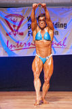 Female bodybuilder flexes her muscles to show her physique Stock Images