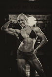 Female Bodybuilder Flexing Muscles Royalty Free Stock Photography