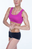Female bodybuilder flexing in sports bra and shorts Stock Image