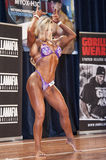 Female bodybuilder in front double biceps pose and pink bikini Stock Images