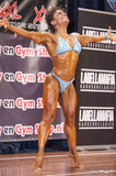 Female bodybuilder in happy and sexy pose and blue bikini Stock Image