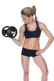 Female bodybuilder holding large black dumbbell with arm up looking at bicep Royalty Free Stock Photography