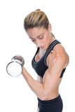 Female bodybuilder holding a large dumbbell looking at bicep Royalty Free Stock Images