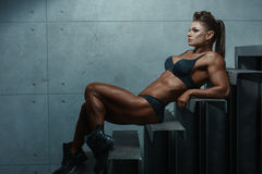 Female bodybuilder lying on the steps. stock photography
