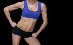 Female bodybuilder posing with hands on hips mid section Stock Image