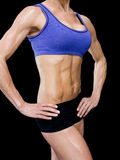 Female bodybuilder posing with hands on hips mid section Royalty Free Stock Images