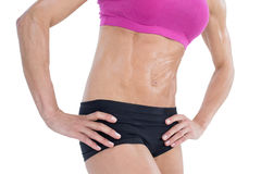 Female bodybuilder posing with hands on hips mid section Stock Photos