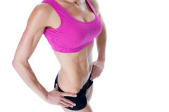Female bodybuilder posing in pink sports bra mid section Stock Images