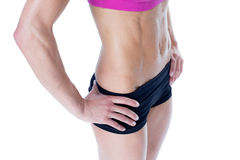 Female bodybuilder posing in pink sports bra and shorts mid section Stock Image
