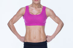 Female bodybuilder posing in pink sports bra and shorts mid section Stock Photo