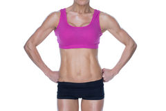 Female bodybuilder posing in pink sports bra and shorts mid section Stock Images