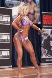 Female bodybuilder posing on stage in pink bikini Royalty Free Stock Photos