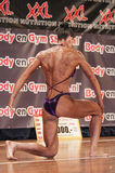 Female bodybuilder in purple bikini performing on stage Royalty Free Stock Photo