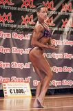 Female bodybuilder in purple bikini performing on stage Stock Photography