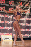Female bodybuilder in purple bikini performing on stage Stock Photos