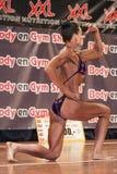 Female bodybuilder in purple bikini shows het big biceps Stock Photos
