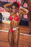 Female bodybuilder in red bikini and abdominals and thighs pose Stock Photos
