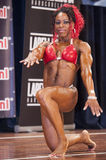 Female bodybuilder in red bikini performing on stage Royalty Free Stock Images