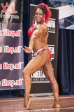 Female bodybuilder in red bikini performing on stage Royalty Free Stock Photography