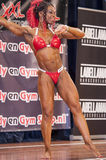 Female bodybuilder in red bikini performing on stage Stock Photos