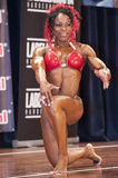 Female bodybuilder in red bikini posing on stage Royalty Free Stock Image
