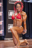 Female bodybuilder in red bikini shows her big triceps Royalty Free Stock Photos