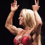 Female bodybuilder shows her double biceps pose in closeup Stock Images
