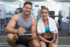 Female bodybuilder sitting with personal trainer smiling at camera Royalty Free Stock Photos
