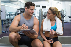 Female bodybuilder sitting with personal trainer talking Stock Photo