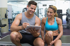 Female bodybuilder sitting with personal trainer talking Royalty Free Stock Photo