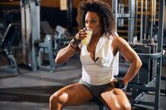 Female bodybuilder taking a sip of a protein drink
