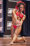 Female bodybuilder in triceps and chest pose and red bikini Stock Photos