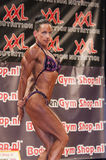 Female bodybuilder in triceps pose and purple bikini Royalty Free Stock Photos