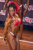 Female bodybuilder in triceps pose and red bikini Royalty Free Stock Image
