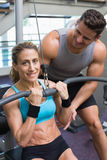Female bodybuilder using weight machine for arms with encouraging trainer Stock Photography