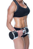 Female bodybuilder working out with large dumbbells mid section Stock Image