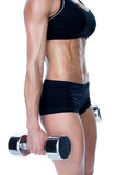 Female bodybuilder working out with large dumbbells mid section Stock Photography