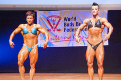 Female bodybuilders flex their muscles to show their physique Royalty Free Stock Image