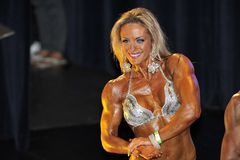 Female bodybuilding contestant showing her chest pose. ROOSENDAAL, THE NETHERLANDS - OCTOBER 19, 2014. Walters Open Dutch Championship 2014 - category Stock Photos
