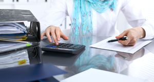 Female bookkeeper or financial inspector  making report, calculating or checking balance. Internal Revenue Servic Royalty Free Stock Photography