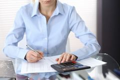 Female bookkeeper or financial inspector  making report, calculating or checking balance. Internal Revenue Servic. E checking financial document. Audit concept Royalty Free Stock Photography