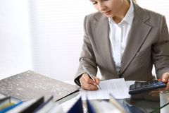 Female bookkeeper or financial inspector  making report, calculating or checking balance. Internal Revenue Servic. E checking financial document. Audit concept Royalty Free Stock Image