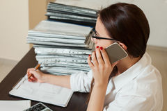 Female bookkeeper in glasses talking by phone Royalty Free Stock Photo