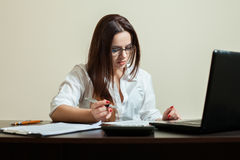 Female bookkeeper in glasses using laptop Stock Photo