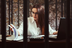 Female bookkeeper, illegal accounting concept. Female bookkeeper working behind bars. Illegal accounting concept stock photo