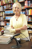 Female bookshop proprietor. With smiling with crossed arms Royalty Free Stock Photography